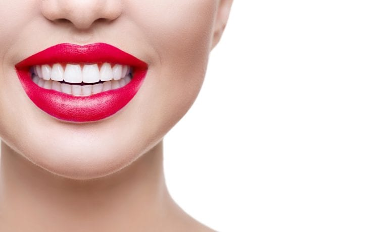 Smiling with red lips on the left side of the page against a white background